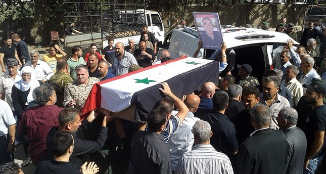 A handout picture released by the regime's Syrian Arab News Agency (SANA) shows Syrians carrying a coffin of a suicide attack victim during a mass funeral in the southern city of Sweida on July 26, 2018. (AFP Photo)