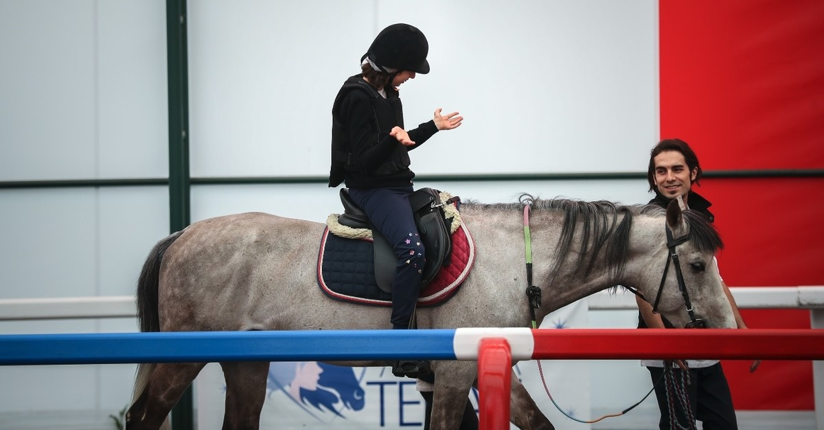 A disabled child enjoys riding a horse at the Horse Therapy Center in Veliefendi Hippodrome, Istanbul.