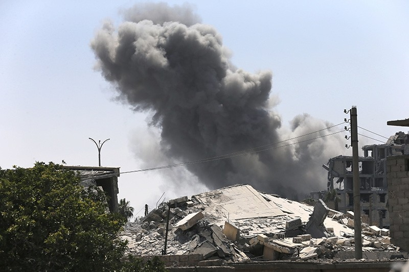 In this July 26, 2017 file photo, black smoke rises from a coalition airstrike which attacked an Islamic State militant position, on the front line on the eastern side of Raqqa, Syria. (AP Photo)