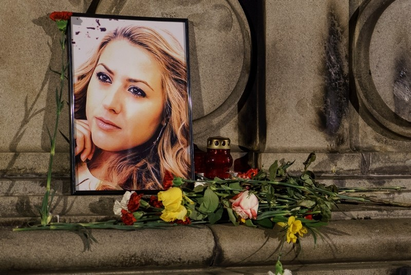 A portrait of slain television reporter Viktoria Marinova is placed on the Liberty Monument next to flowers and candles during a vigil in Ruse, Bulgaria, Tuesday, Oct. 9, 2018. (AP Photo)