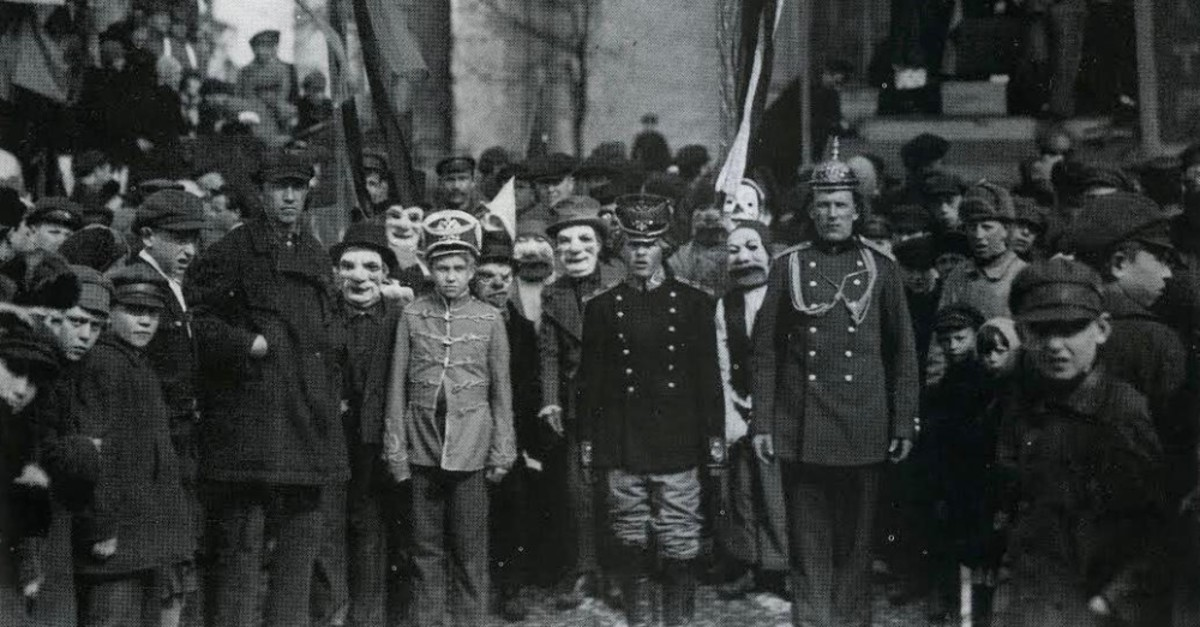Demonstrators with Stem Masks, Leningrad, May 1, 1924. On the left side of the mask, the slogan- ,I'm buying from a private seller, on the right- ,I consume cooperative goods, Krasnaya Gazeta, May 2, 1925.