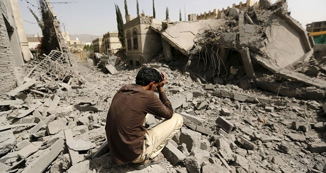 A guard sits on what is left of the house of Brigadier Fouad al-Emad, army commander loyal to the Houthis, after Saudi-led air strikes destroyed it in Sanaa. Reuters Photo