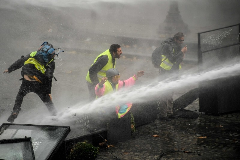 Yellow vests (Gilet jaune) protestors are showered by a water cannon near the Place de la Concorde in Paris, on November 24, 2018, during a protest against rising oil prices and living costs. (AFP Photo)