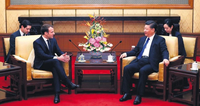 French President Emmanuel Macron (L) chats with Chinese President Xi Jinping during a meeting at the Diaoyutai State Guesthouse, Beijing,  Jan. 8.