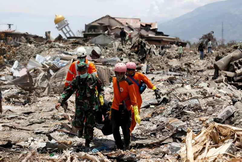 Rescue workers and a soldier remove a victim of last week's earthquake in the Balaroa neighbourhood in Palu, Central Sulawesi, Indonesia October 6, 2018. (REUTERS Photo)