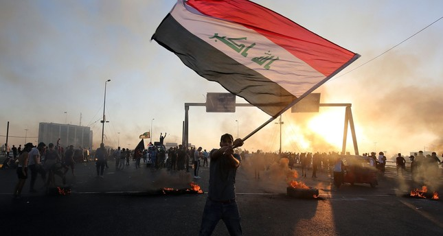 An Iraqi protester waves the national flag during anti-government demonstrations, Baghdad, Oct. 5, 2019.