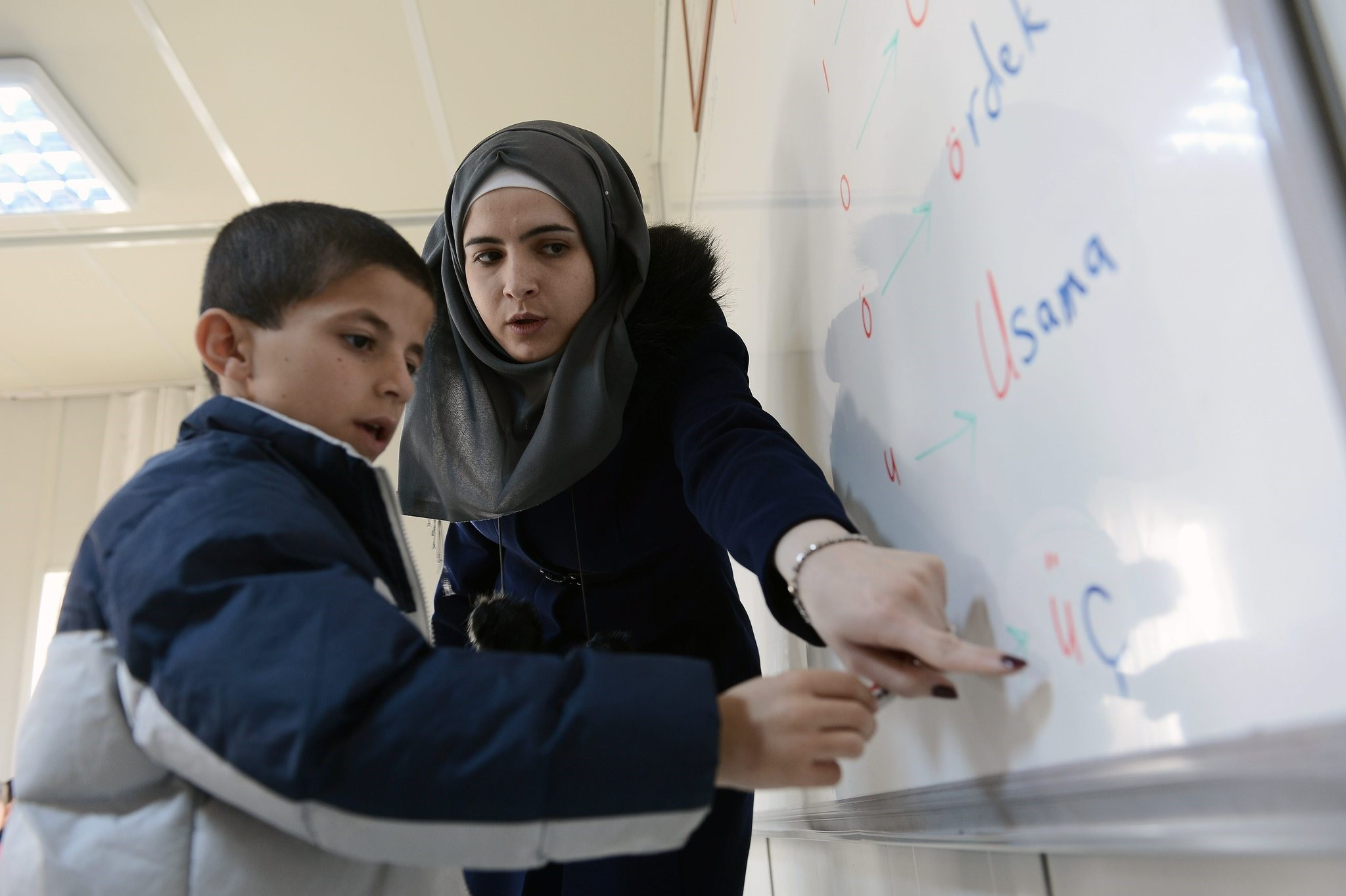 A Syrian teacher with a Syrian student at a school inside a refugee camp in the eastern city of Malatya.