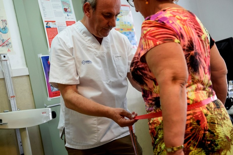 Doctor Carlos Pineiro weighs a woman at the town's health center in Naron, on September 13, 2018. (AFP Photo)