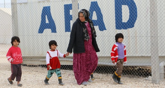 A Syrian refugee woman walks with children at a refugee camp in Şanlıurfa. Women and children make up three quarters of the refugee population according to UNHCR.