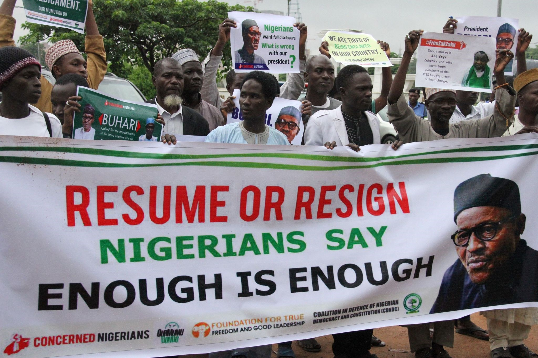 Protesters carry placards to demand that ailing President Buhari resume work or resign in Abuja, on August 7, 2017. (AFP Photo)