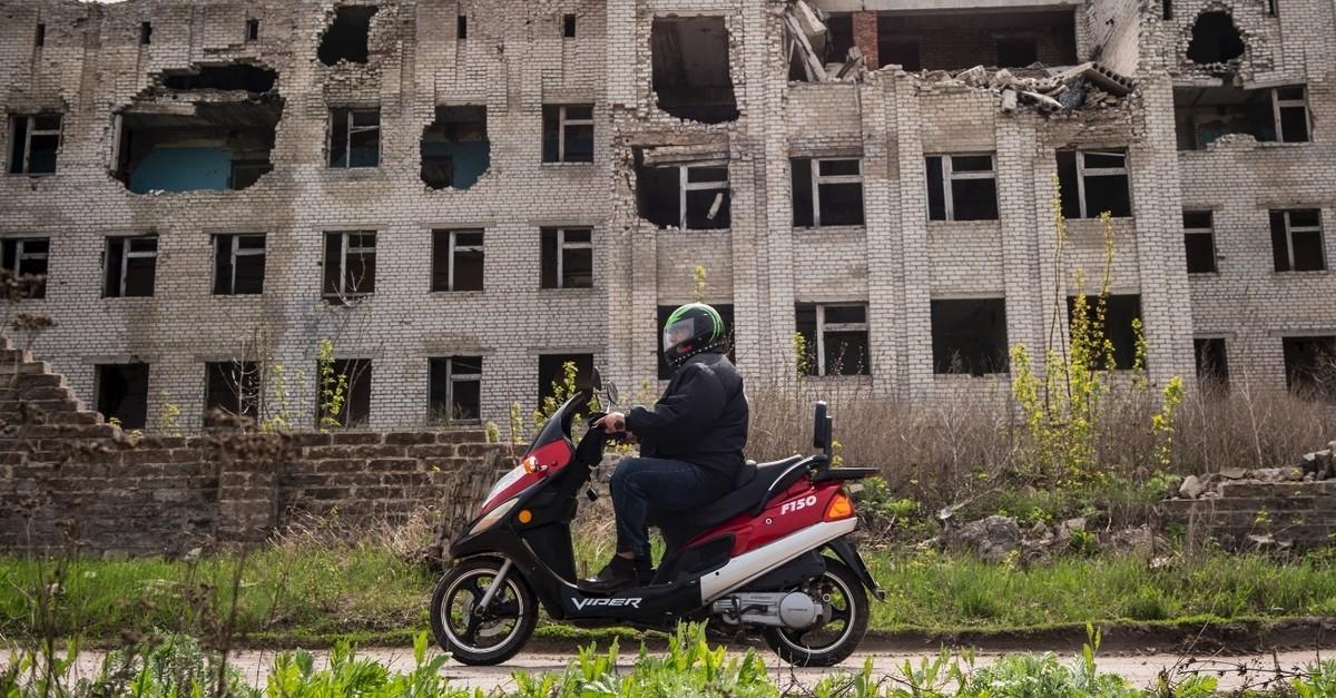 A cyclist rides his motorbike near a destroyed hospital, Slovyansk, Donetsk region, April 19, 2019.