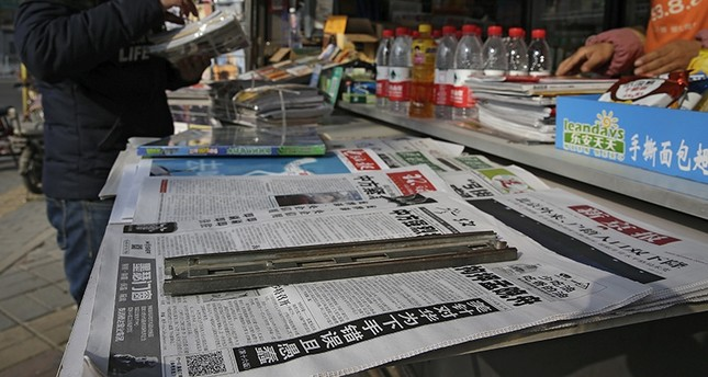 A man arranges magazines near newspapers with the headlines of China outcry against U.S. on the detention of Huawei's chief financial officer, Meng Wanzhou, at a news stand in Beijing, Monday, Dec. 10, 2018. (AP Photo)