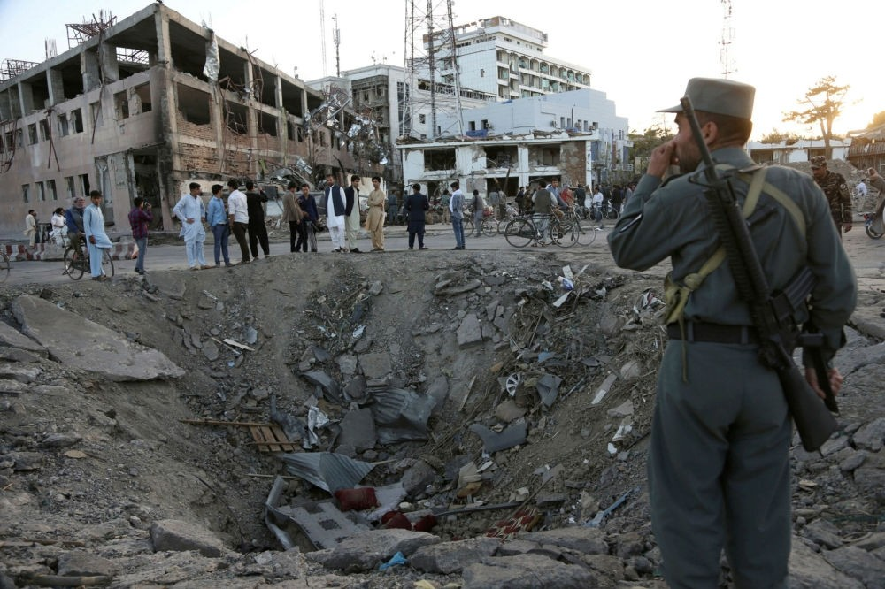 Security forces stand next to a crater created by a massive explosion, that killed over 150 in front of the German Embassy in Kabul, Afghanistan on May 31.