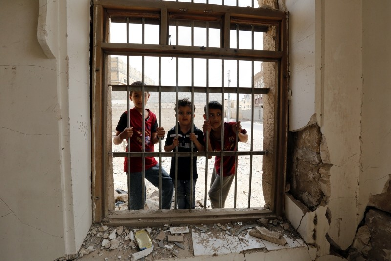 Three Yemeni children stand behind a window of a destroyed building allegedly hit by a previous Saudi-led airstrike, in Sanaa, Yemen. (AFP Photo)