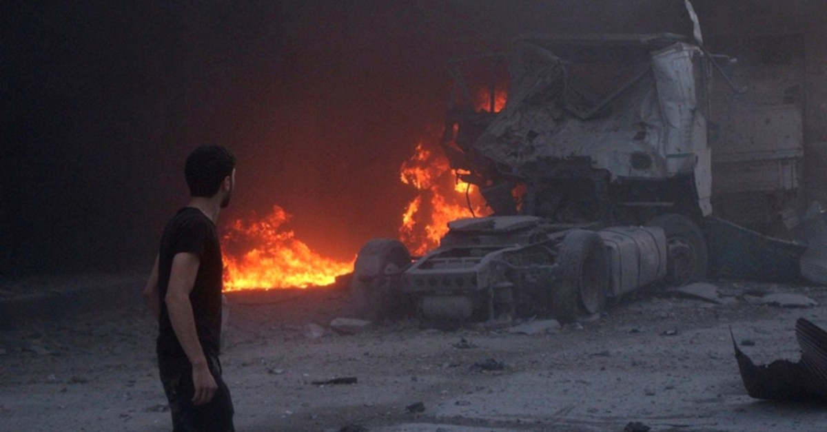 People walk next to fire, debris and a damaged truck after a deadly airstrike, said to be in Maarat al-Numan, Idlib province, Syria August 28, 2019. (AP Photo)