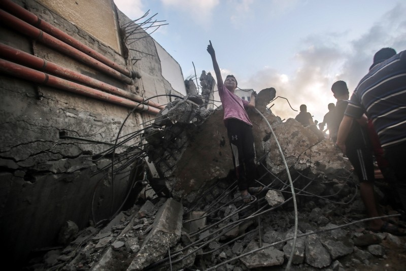 Palestinians inspect Said al-Mishal Cultural Center building destroyed in Israeli air strike in the west of Gaza City, 09 August 2018. Reports say 18 Palestinians were wounded in the strike on alleged Hamas HQ at the Al-Shati Camp. (EPA Photo)