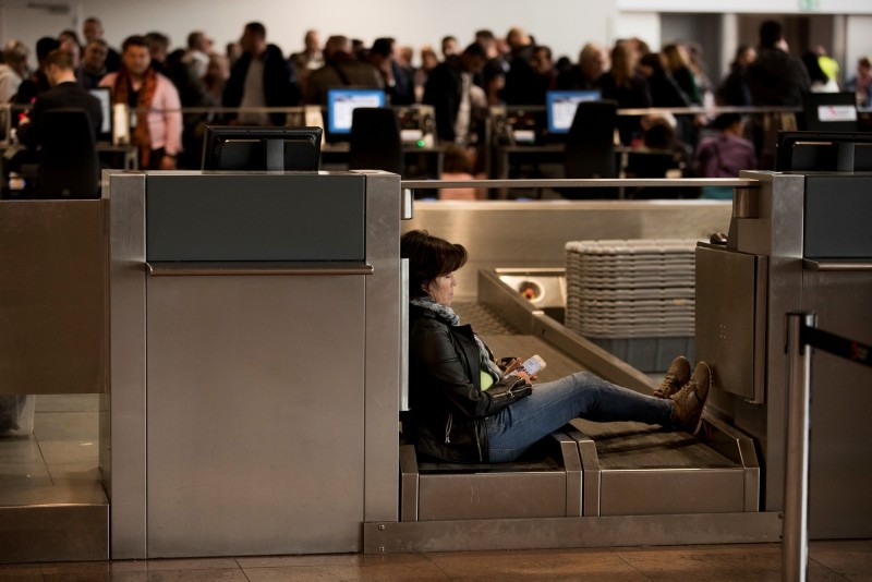 A woman sits in a check-in desk of the departures hall of the Zaventem international airport during a luggage handling workers strike in Brussels. (AP Photo)