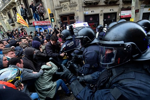 Protesters scuffle with riot police blocking the road leading to the central government offices at a demonstration in Barcelona on March 25, 2018 (AFP Photo).