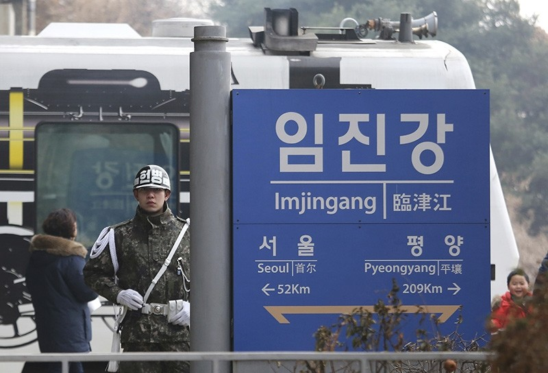 In this Jan. 14, 2018, file photo, a South Korean army soldier stands guard next to a signboard showing the distance to North Korea's capital Pyongyang and to South Korea's capital Seoul (AP Photo)