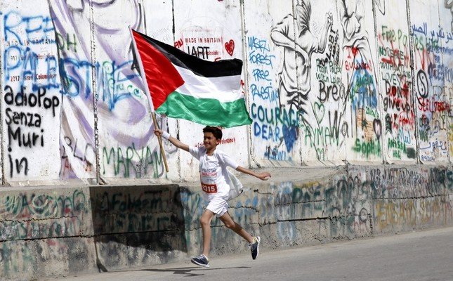 A child runs holding the Palestinian flag as he passes graffiti on the controversial Israeli separation barrier during the Palestine Marathon, Bethlehem, March, 2018.