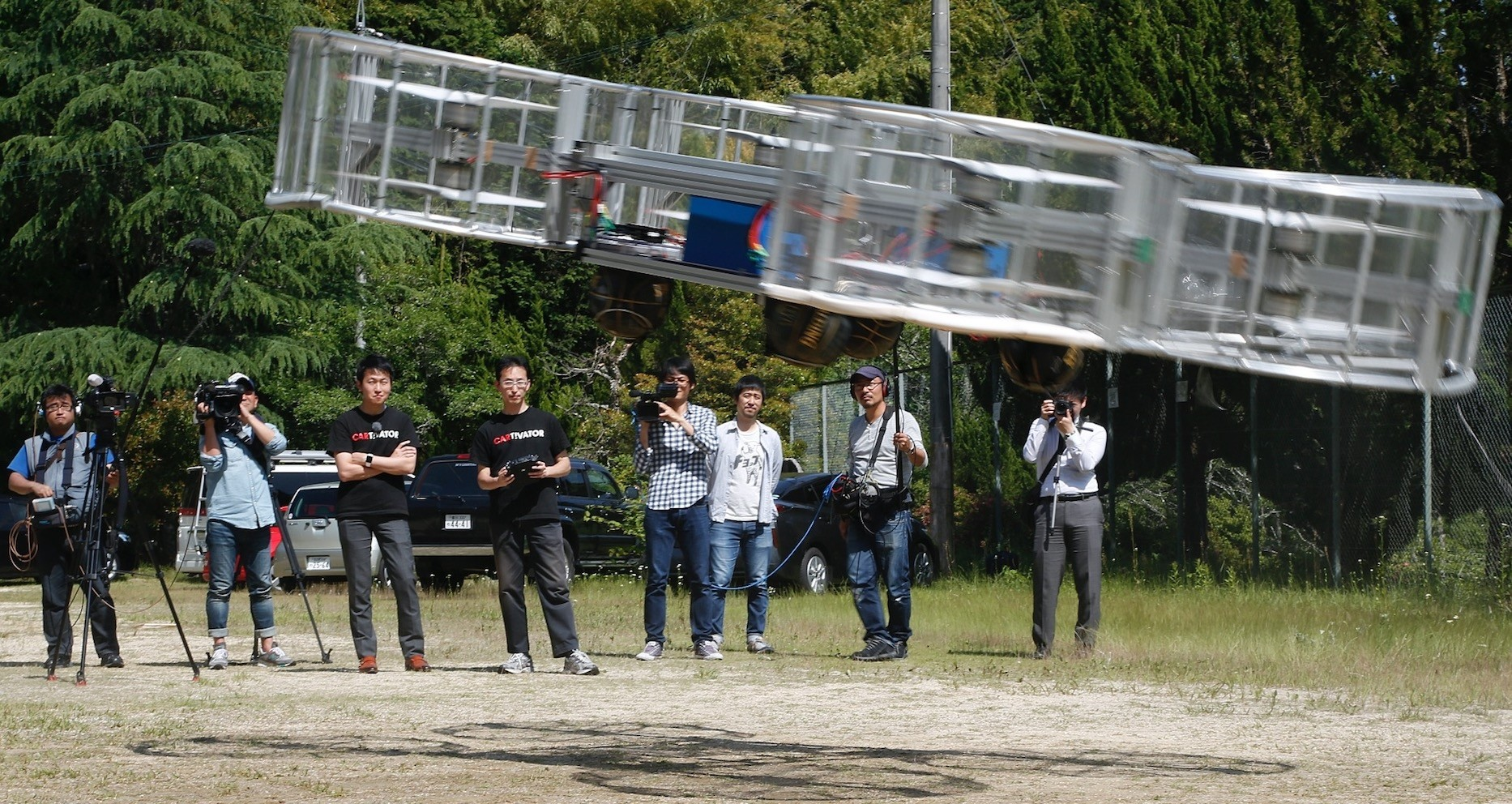 Tsubasa Nakamura, project leader of Cartivator, third from left, watches the flight of the test model of the flying car on a former school ground in Toyota, central Japan.