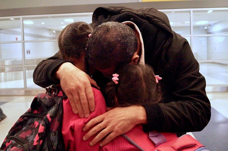 Fadi Kassar (L) hugs his daughters Hnan, 8 and Lian, 5, for the first time in more than 2 years after the family was reunited. (REUTERS Photo)