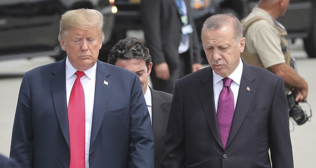 U.S. President Donald Trump (L) and President Recep Tayyip Erdoğan (R) talk while walking to attend NATO's Brussels Summit, Belgium, July 11.