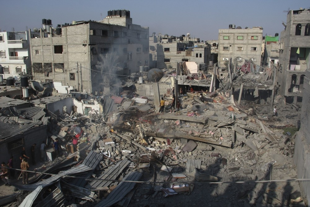 Palestinians stand on the rubble of houses destroyed in an Israeli strike in Rafah, southern Gaza Strip, Aug. 2, 2014.