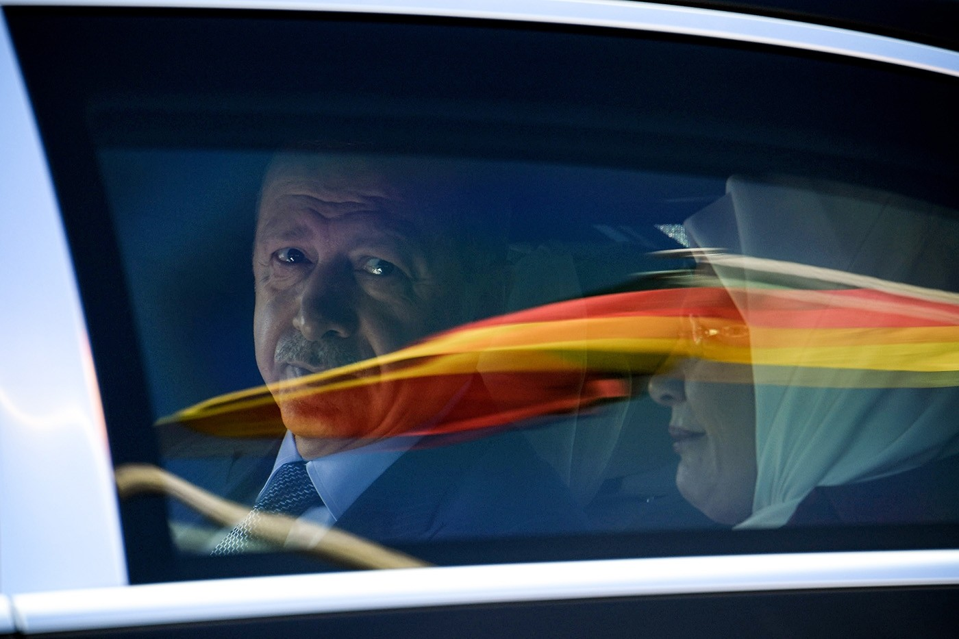President Recep Tayyip Erdoğan sits in a car behind a reflection of the German flag as he departs after his arrival from the Berlin Tegel Airport for an official visit in Berlin, Germany, 27 September 2018. (EPA Photo)