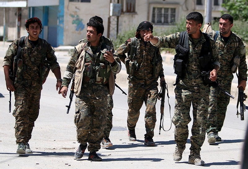 YPG terrorists walk along a street in the southeast of Qamishli city, Syria (Reuters File Photo)
