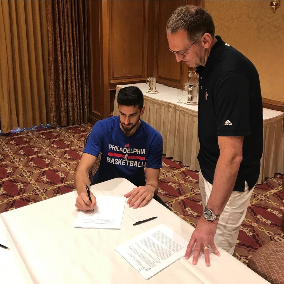 Furkan Korkmaz signing his contract with Philadelphia 76ers President of Basketball Operations Bryan Colangelo. (Photo: @sixers Twitter account)