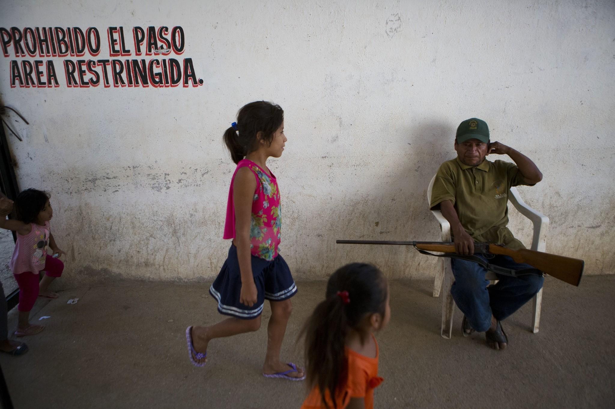 In this Feb. 4, 2018, photo, children walk past a ,community police, officer at the vigilante force's base in Ayutla de los Libres, Guerrero state, Mexico. (AP Photo)