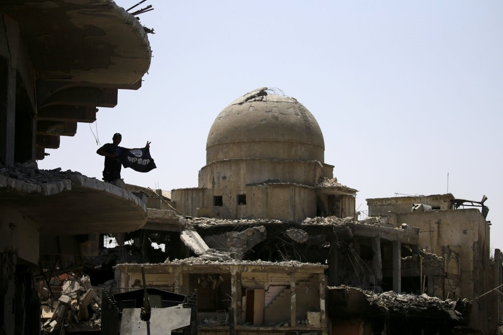 A member of Iraqi security forces holds a Daesh flag on the top of a building destroyed in clashes in the old city of Mosul, Iraq July 10.