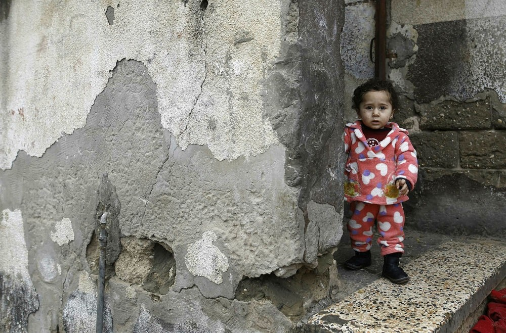 A Palestinian toddler stands outside her family home at the al-Shati refugee camp, Gaza City, Jan. 17.