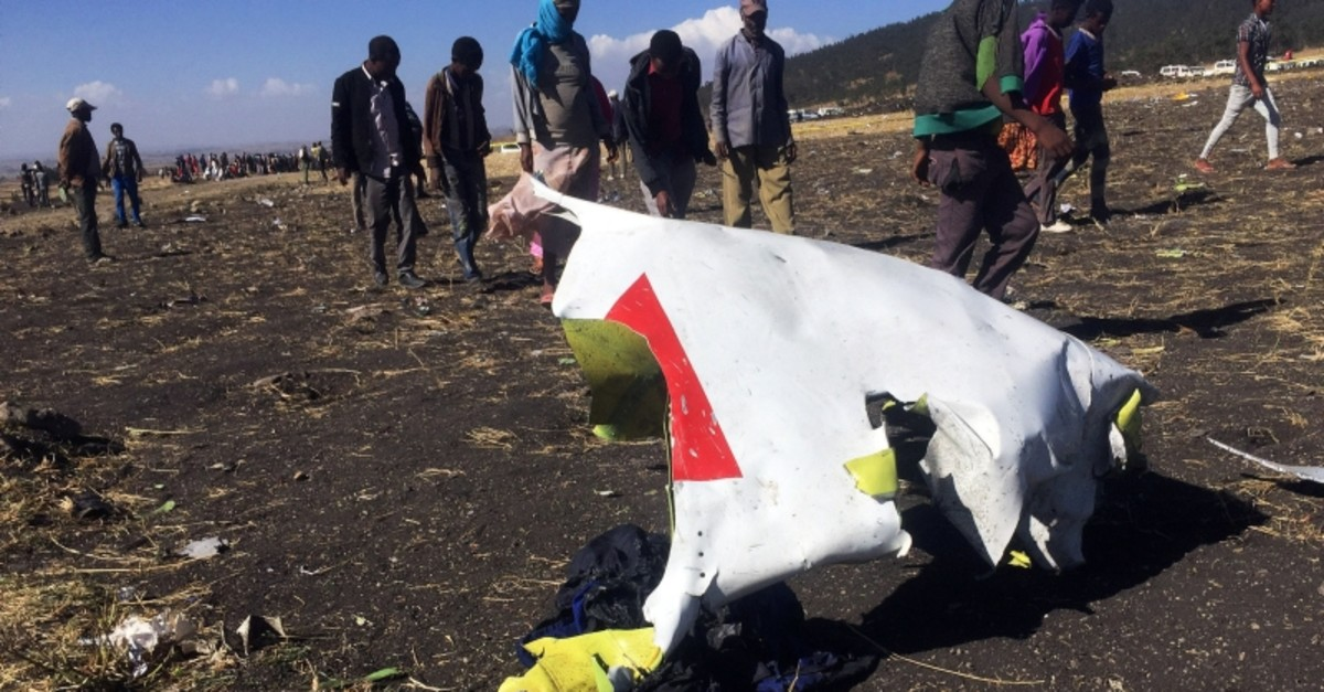 People walk past a part of the wreckage at the scene of the Ethiopian Airlines Flight ET 302 plane crash, near the town of Bishoftu, southeast of Addis Ababa, Ethiopia March 10, 2019. (Reuters Photo)