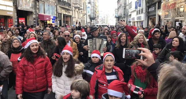 Children and adults sing carols on İstiklal Avenue.