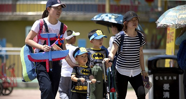 In this June 1, 2018, photo, women walk with children wearing matching outfits at a public park on International Children's Day in Beijing. (AP Photo)