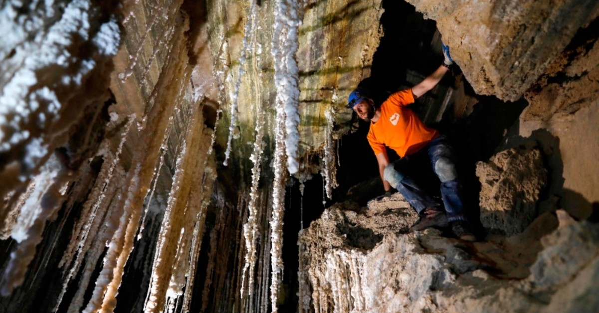 Efraim Cohen of the Israel Cave Explorers Club, and of the Malham Cave Mapping Expedition, shows journalists salt stalactites in the Malham cave inside Mount Sodom, located at the southern part of the Dead Sea in Israel on March 27, 2019. (AFP Photo)