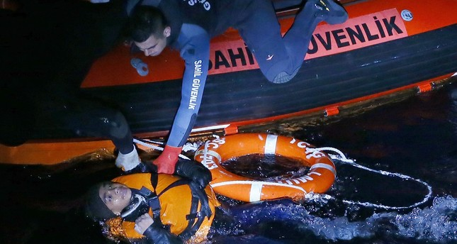 A Coast Guard officer pulls a migrant to safety from a sinking boat off the coast of Çeşme district of İzmir.