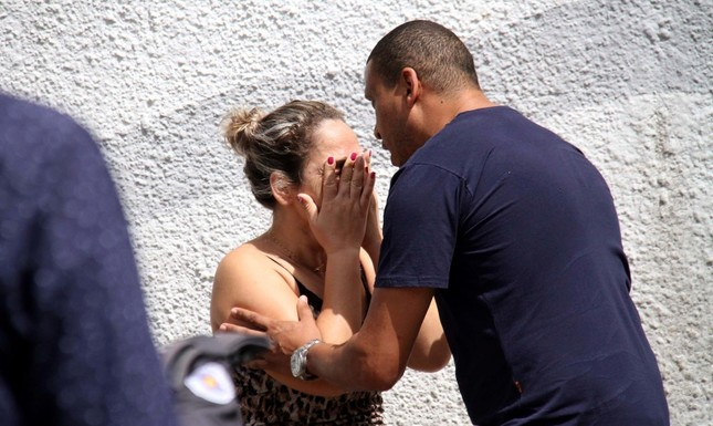A man comforts a woman at the Raul Brasil State School in Suzano, Brazil, Wednesday, March 13, 2019. (AP Photo)