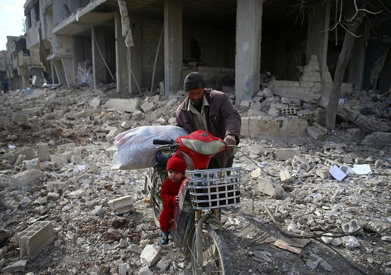A man is seen with a child who rides a bicycle inside damaged area in Misraba, Eastern Ghouta, near Damascus, Syria January 11, 2018. (Reuters Photo)