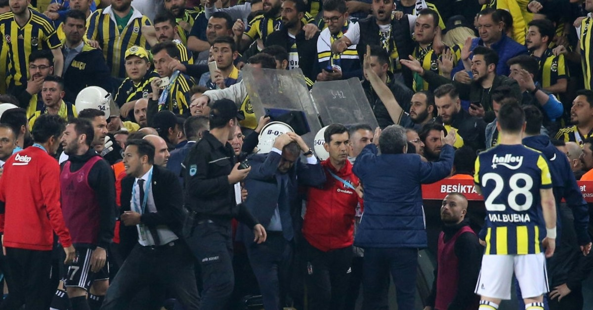 Beu015fiktau015f coach u015eenol Gu00fcneu015f (center) holds his head after being hit by an object hurled by fans during a match against Fenerbahu00e7e in Istanbul, April 19, 2018.
