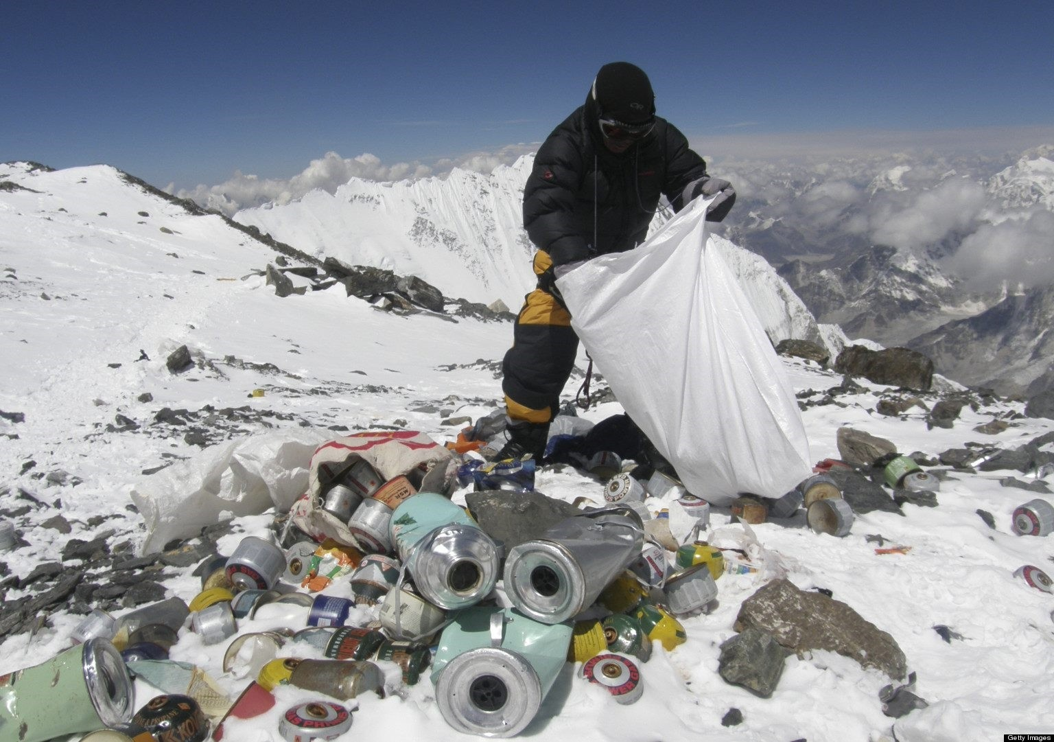 A Nepalese sherpa collects garbage left by climbers on Mount Everest.