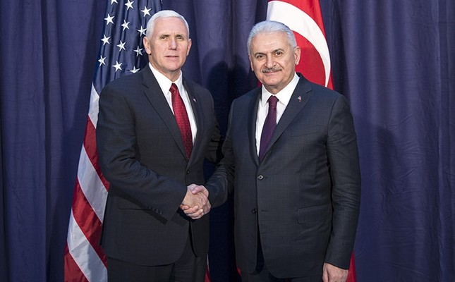 US Vice President Mike Pence (L) and Prime Minister Binali Yıldırım shake hands for the photographers prior to their meeting during the Munich Security Conference in Munich, Germany, Saturday, Feb. 18, 2017. (Prime Minister's Press Service via AP)