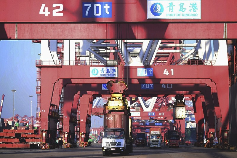 Trucks move shipping containers at a port in Qingdao in eastern China's Shandong province. (Chinatopix Photo via AP)
