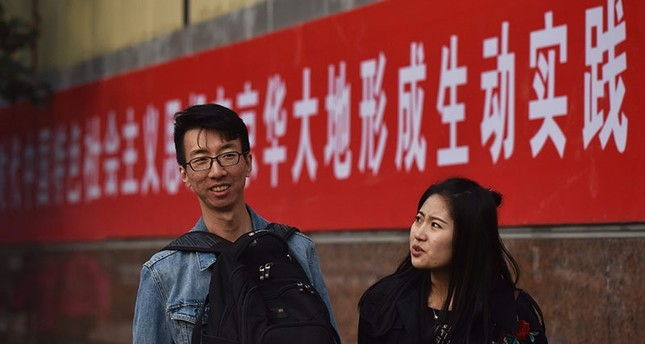 Students walk by characters reading Promote Xi's thought of socialism with Chinese characteristics in the new era, making it a lively practice in Beijing. (AFP Photo)