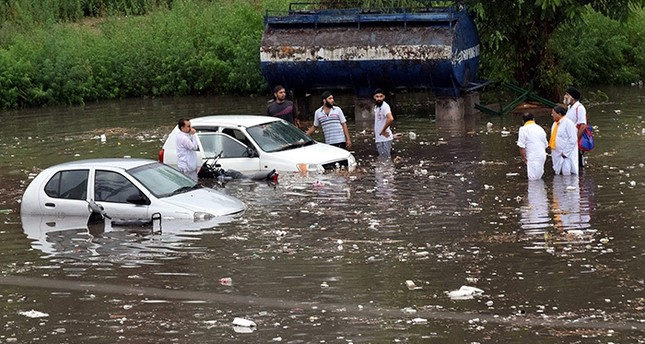 Indian people stands with their drowned vehicles at parking of Maulana Azad Stadium after a heavy monsoon shower in Jammu, the winter capital of Kashmir, India, 21 June 2016. (EPA Photo)