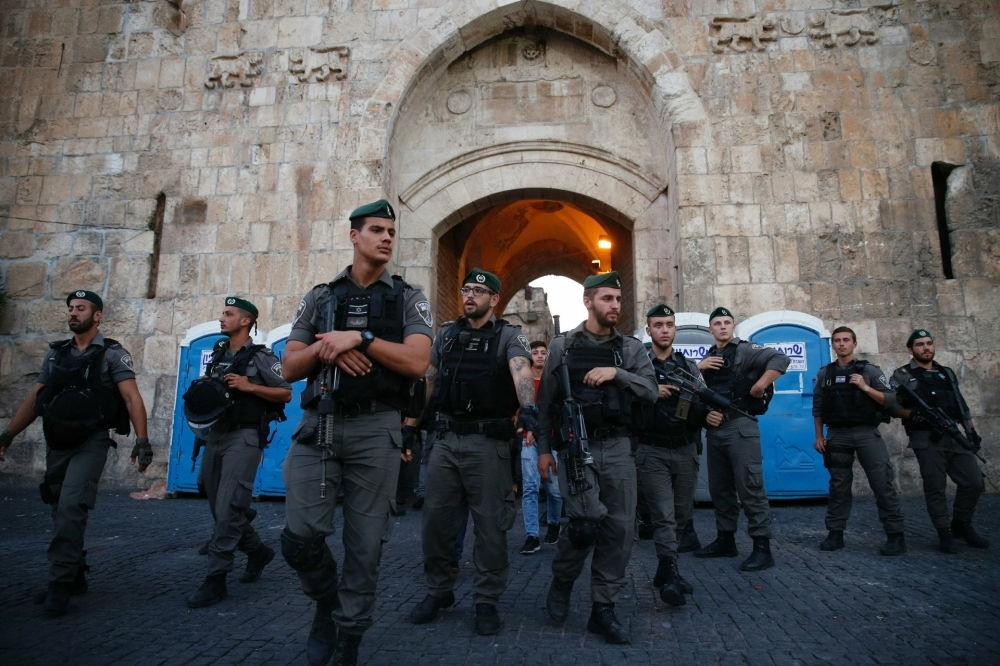 Israeli security forces stand guard as Palestinian worshippers pray next to the Lions Gate, a main entrance to the holy site in Jerusalem's Old City, in July 18.