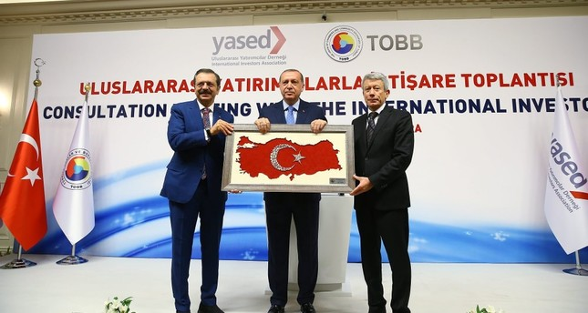 President Erdoğan (C) met foreign investors at the Consultation Meeting with the International Investors and was presented with a gift by Chairman of TOBB Rifat Hisarcıklıoğlu (L) and YASED Chairman Ahmet Erdem (R).