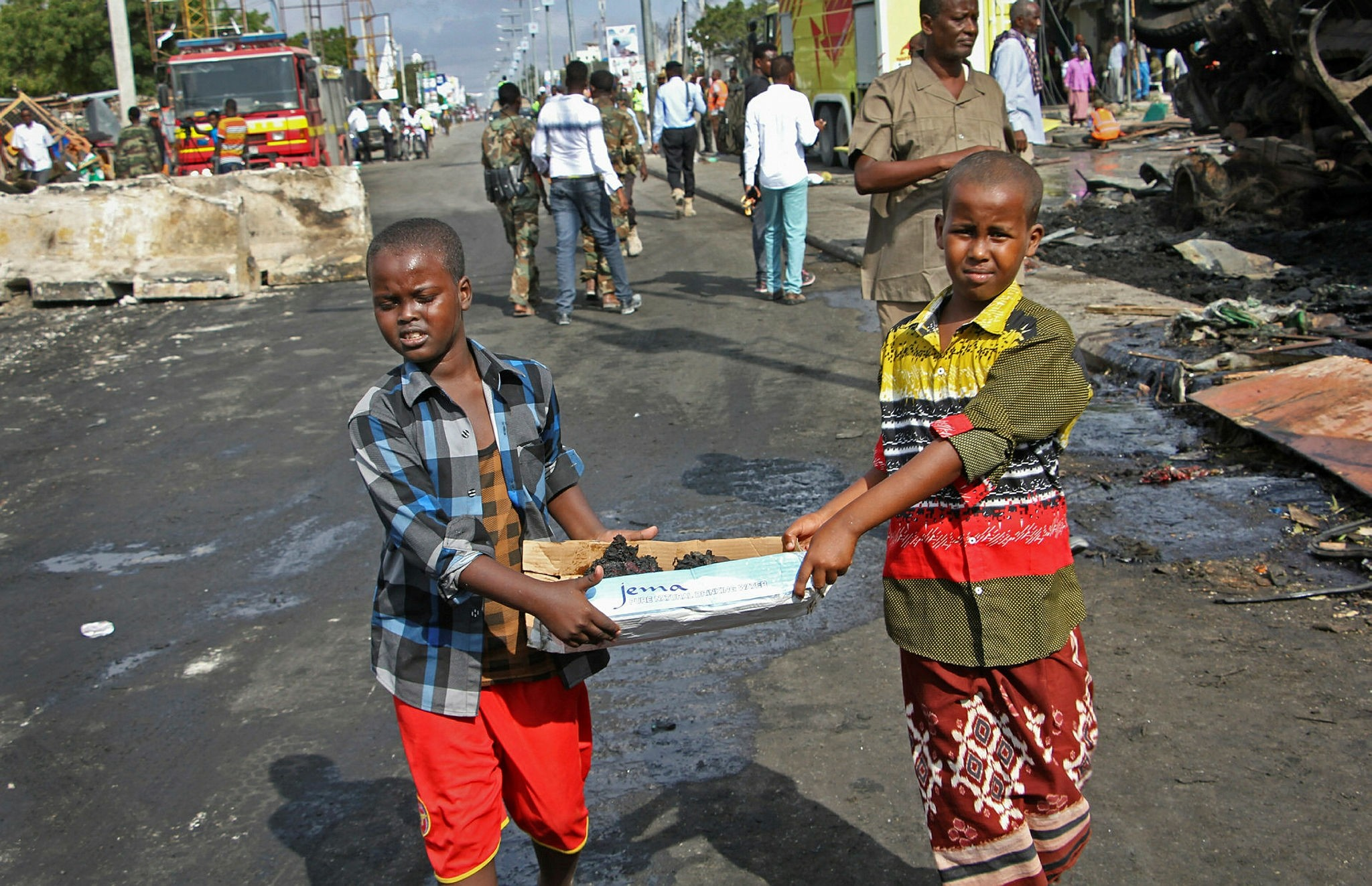 In this 2017 file photo, Somali children assist other civilians & security forces in their rescue efforts by carrying away unidentified charred human remains in a cardboard box, to clear the scene of the previous day's blast, in Mogadishu. (AP Photo)